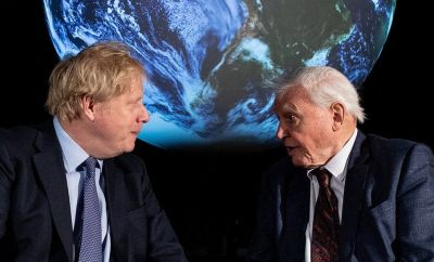 Boris Johnson and David Attenborough talking in front of a projection of Earth