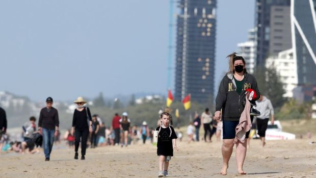 People wearing masks walk along the beach at Surfers Paradise