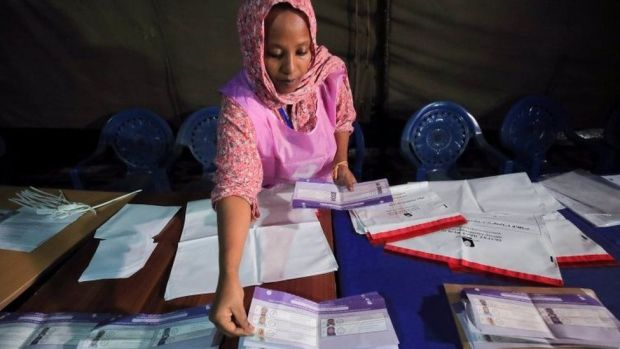 An election official counts voting ballots