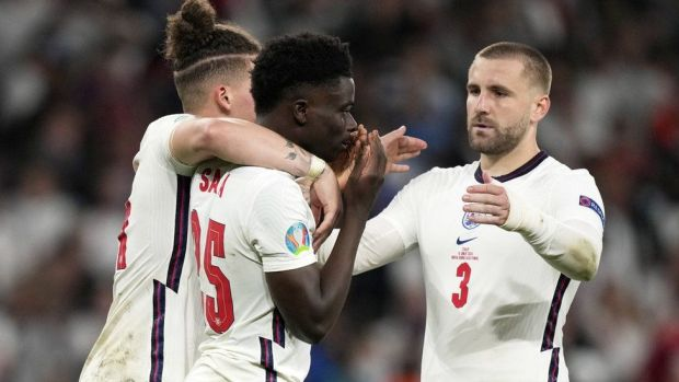Bukayo Saka is consoled by his team-mates