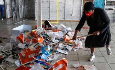 Local woman uses broom to sweep mess inside looted store