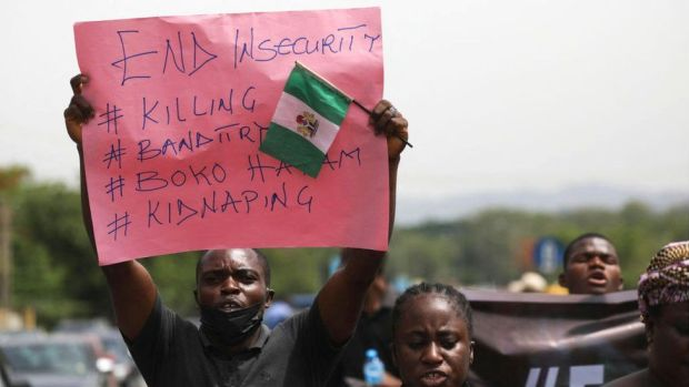 Parents and relatives of abducted students from a different school hold placards during a demonstration in Abuja