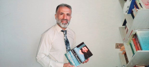 Yassin-with-his-book-Son-of-Mountains-in-his-hands-photo-by-Dana-Taib-Menmy-for-Al-Jazeera-2