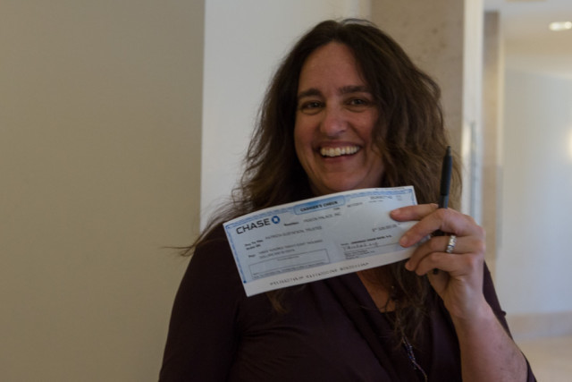 Tenant Carien McKay holds a check for the down payment that will take a Folsom Street building forever out of the private market