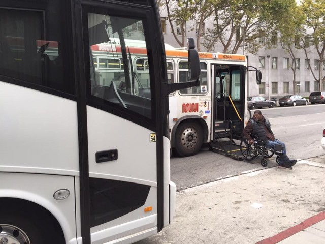 A shuttle bus blocks a Muni stop, forcing a passenger in a wheelchair to get off in the middle of the street