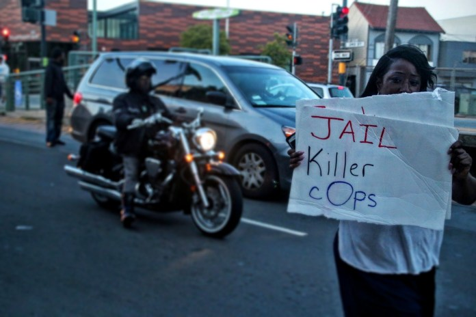 """Protestor holds a sign that says """"Jail killer cops."""" Photo by Sana Saleem"""