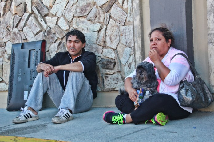 Families wait for transport to Salvation Army Shelter on Saturday evening after the fire. Photo by Sana Saleem