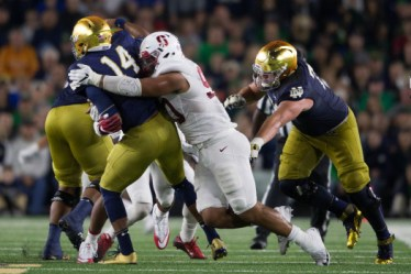 Stanford defensive end Solomon Thomas hits Notre Dame quarterback DeShone Kizer during Saturday's 17-10 victory by the Cardinal in 17-10 in South Bend, Indiana. (Don Feria / isiphotos.com)