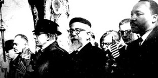 Rabbi Abraham Joshua Heschel (c) marches alongside Dr. Martin Luther King Jr (r) in Selma, AL., March 1965. Photo: Courtesy of Clarion Journal.