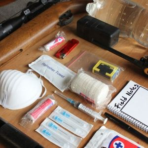 image of face mask and other preparation items for emergency siutations laid out on a table including gauze medical supplies walkie-talkie and others