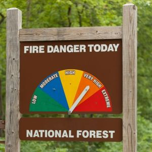 fire danger sign showing a half circle with 5 different color sections with a movable arrow that shows how high the fire danger is today