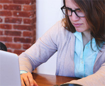 Woman in 20s or 30s with glasses peers at laptop screen.