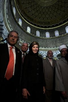 Laura Bush wearing a scarf standing inside Dome of the Rock Mousqe with Muslim Imams