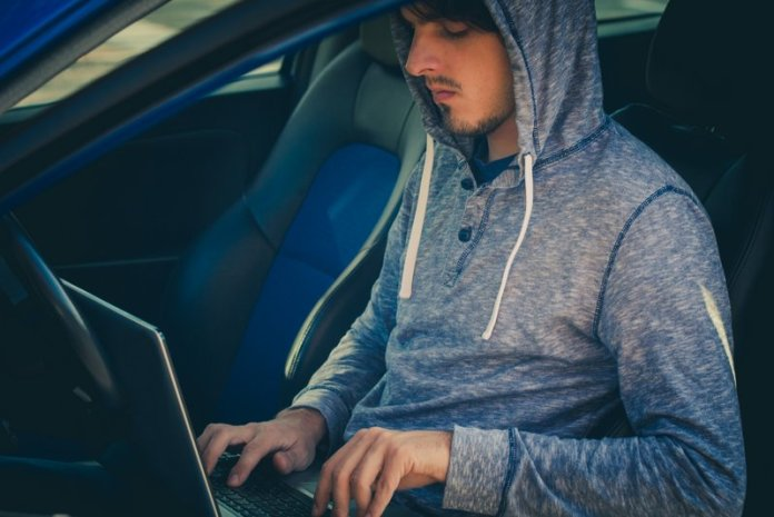 hacker sit in car with his laptop closeup