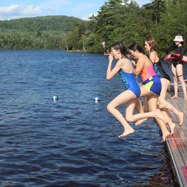A photo that shows all campers jumping into the lake