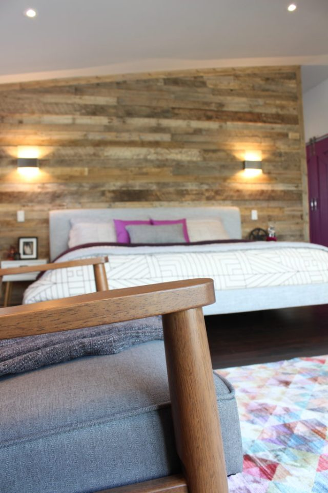 Close up of loveseat with bed and DIY pallet wall in the background | Dream Bedroom Reveal - The Dreamhouse Project
