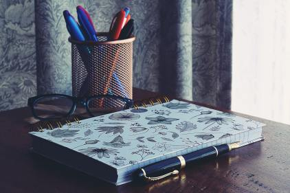 close-up-photography-of-notebook-near-pens