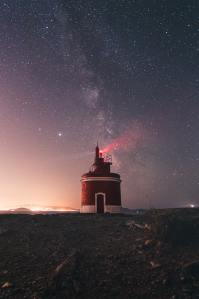 lighthouse-glowing-on-starry-sky