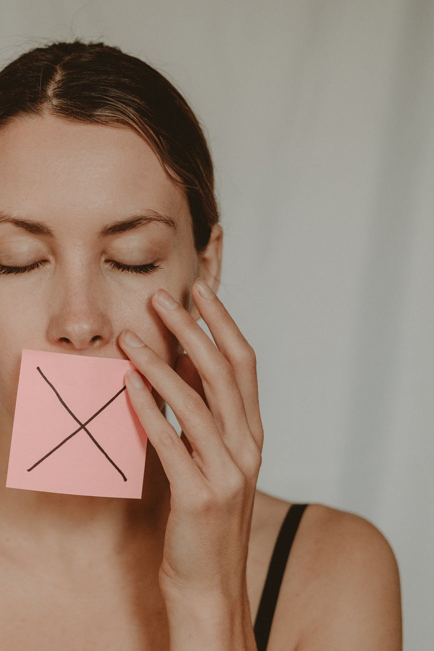woman with cross symbol on mouth unable to speak