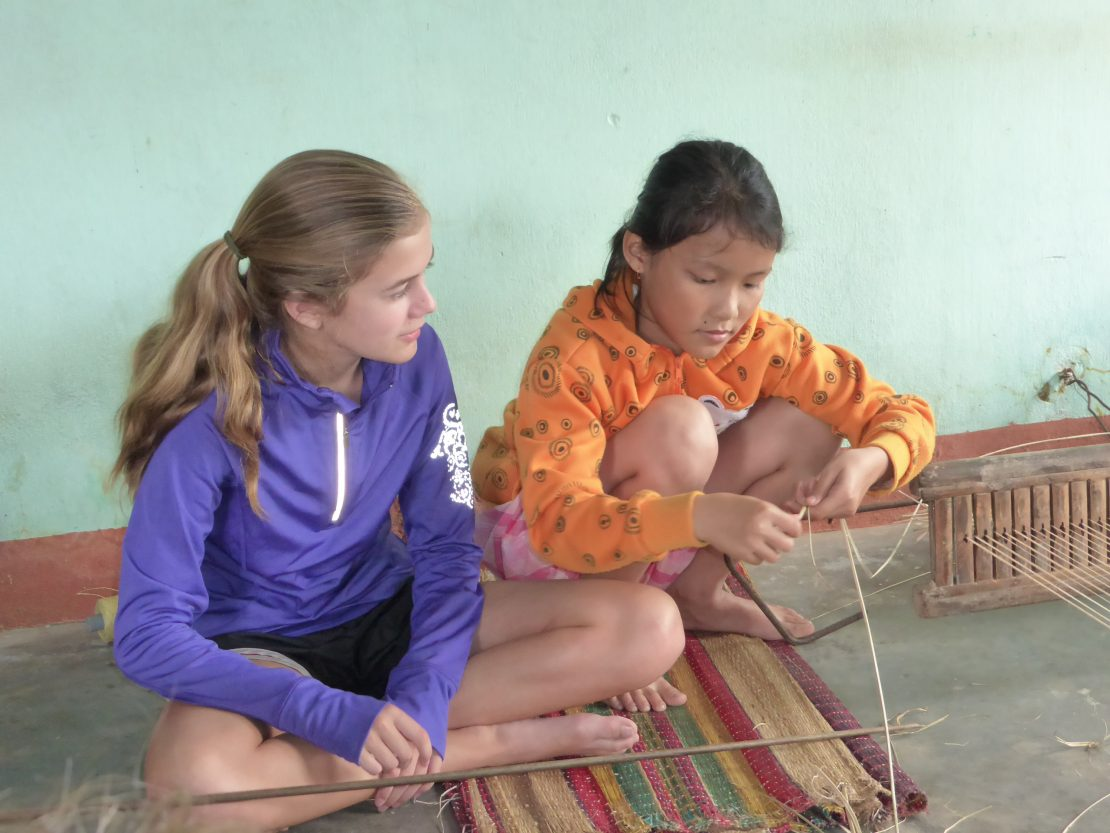 Vietnamese girl teaches American girl how to weave mats
