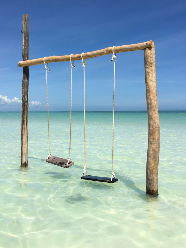 Holbox Island hanging swings over crystal clear shallow beach water