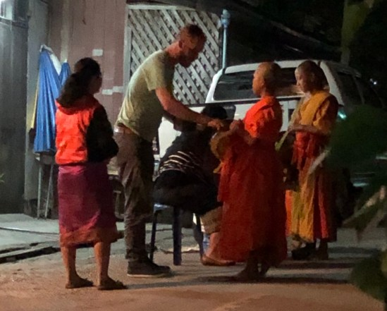 Man giving alms to monks during Tak Bat
