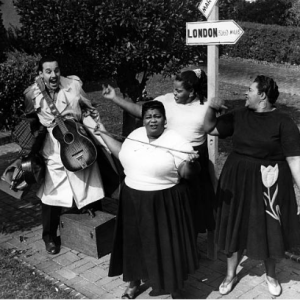 """The Three Tons of Joy by a street sign saying """"London"""", with Johnny Otis running up to them carrying a guitar"""