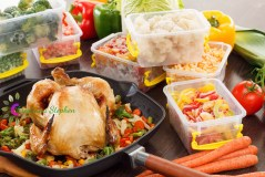 Steam frozen vegetables in plastic containers, roasted chicken in pan. Healthy freezer food and meals.