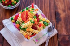 Pasta salad with vegetable on wooden table