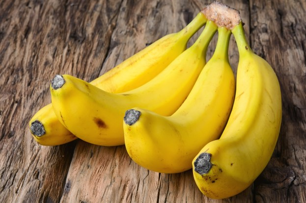 bunches of ripe bananas on vintage wooden background