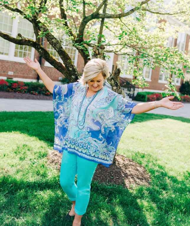 Fashion Blogger 50 is not old in a colorful blue summer poncho enjoying the sunshine.
