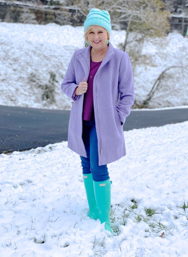 Purple coat and blue boots in the snow