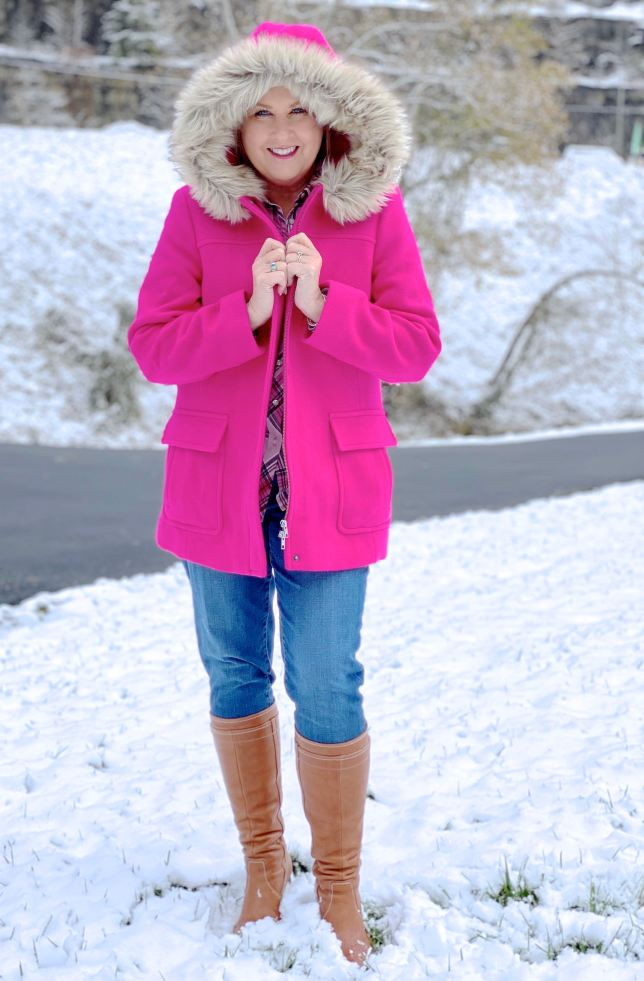A blonde woman in the snow with a bright pink wool coat with a faux fur hood