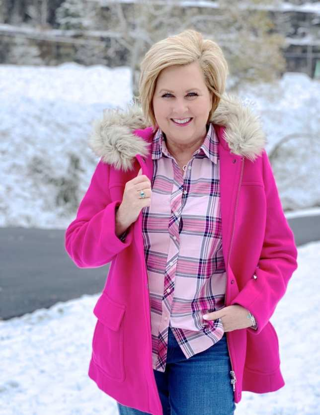A blonde woman in the snow with a bright pink coat with a faux fur hood