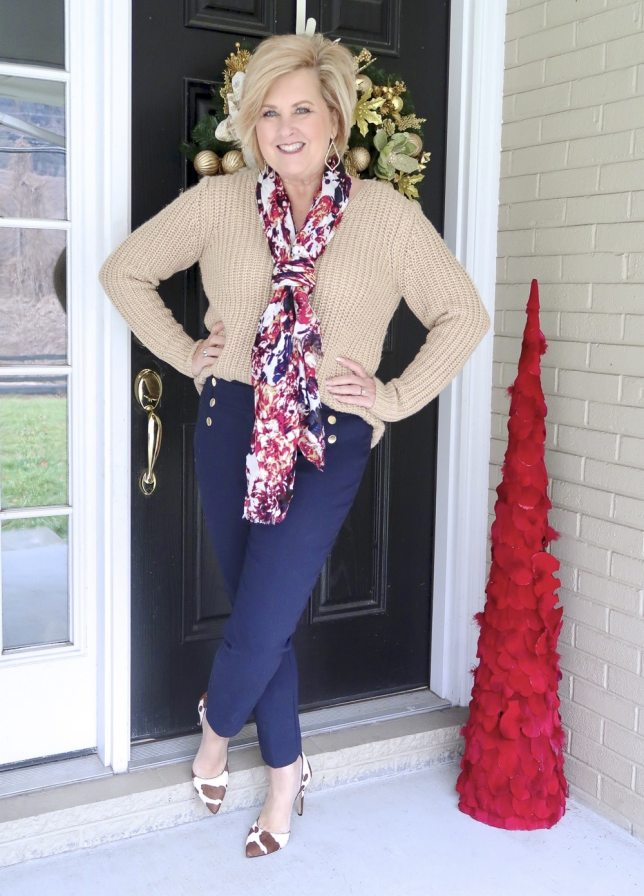 A gold sweater and navy pants with cow print shoes worn by Fashion Blogger 50 Is Not Old
