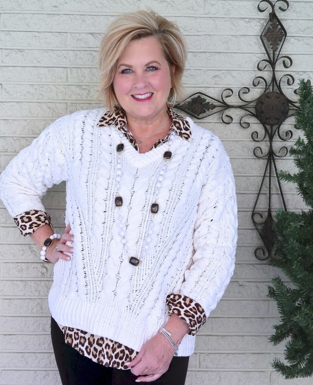 Fashion Blogger 50 Is Not Old wearing an ivory cable knit sweater with a leopard print shirt and brown pants