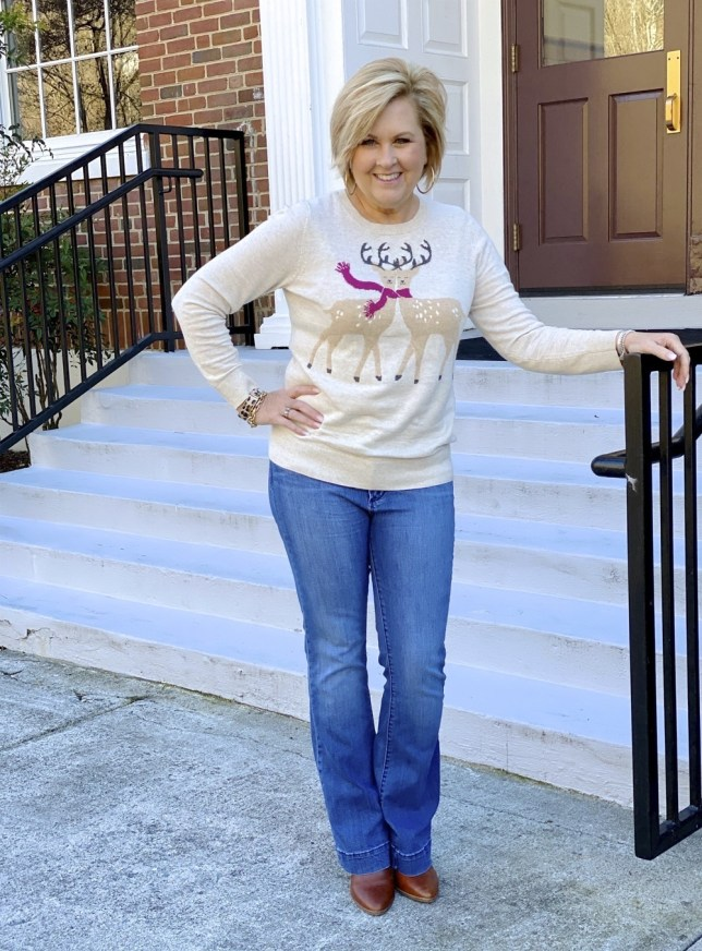 50 Is Not Old Fashion Blogger wearing a Holiday reindeer sweater and flare jeans