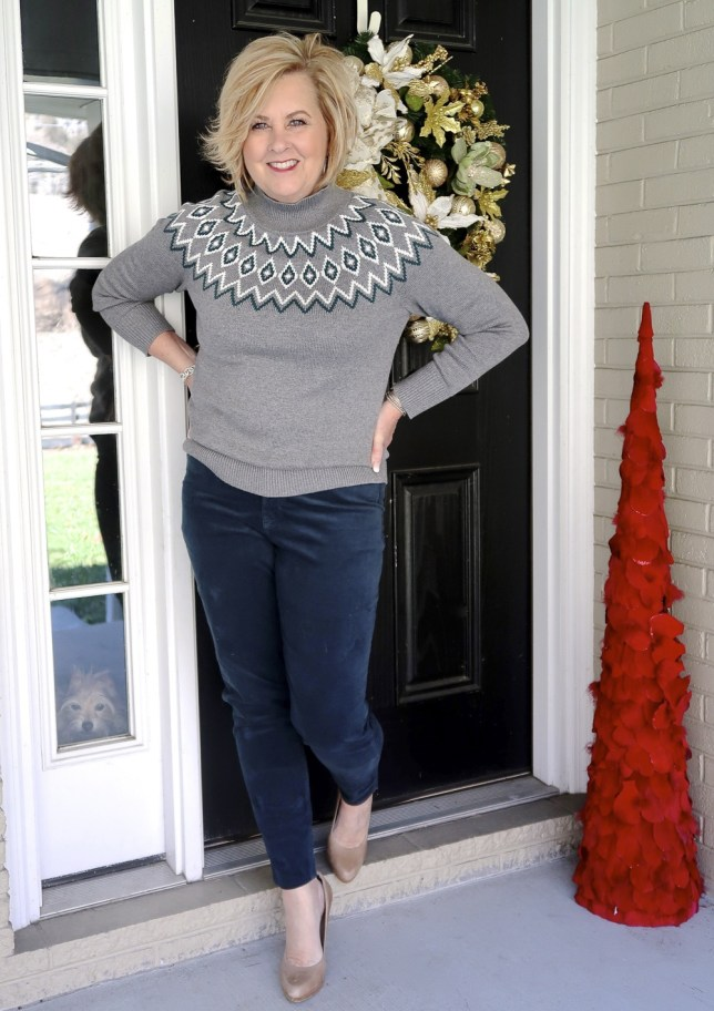 Fashion Blogger 50 Is Not Old wearing a gray sweater with nude pumps and teal pants