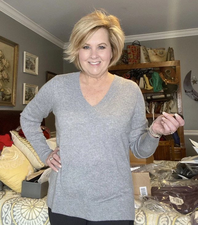 Fashion Blogger 50 Is Not Old holds a try on session with a gray cashmere v-neck sweater