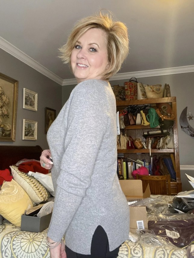 Fashion Blogger 50 Is Not Old holds a try on session shows you the side view of a gray sweater