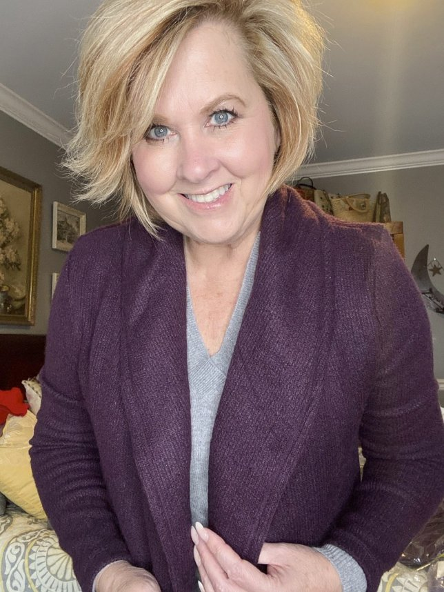 Fashion Blogger 50 Is Not Old holds a try on session wears a deep plum cardigan
