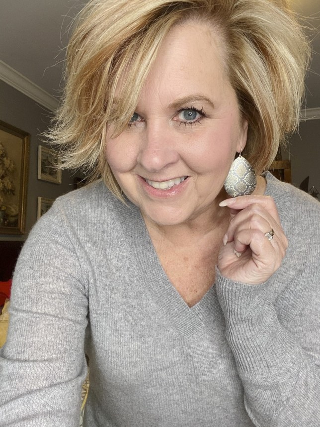 Fashion Blogger 50 Is Not Old holds a try on session shows a snakeskin print metal earring