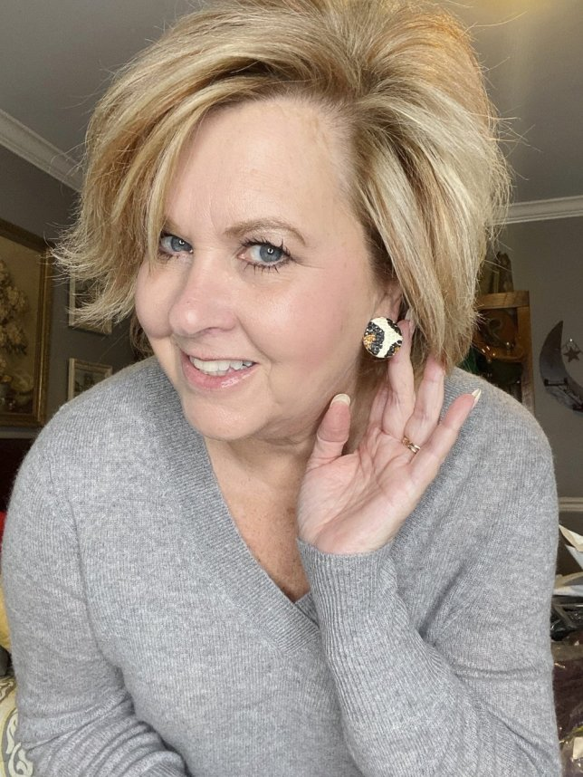 Fashion Blogger 50 Is Not Old holds a try on session shows a leopard print stud earring