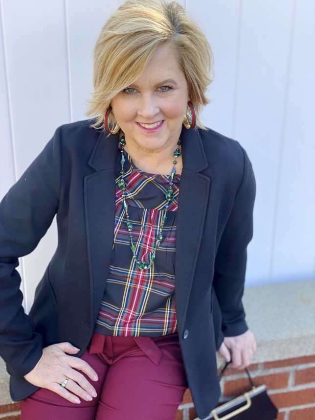 A plaid top and a black blazer worn by Fashion Blogger 50 Is Not Old
