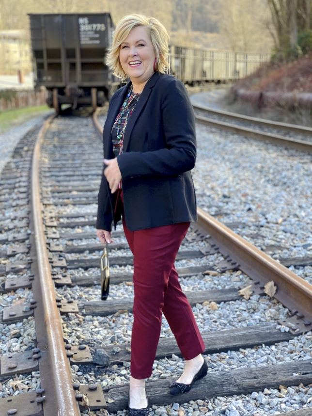 Black blazer and burgundy ankle pants worn by Fashion Blogger 50 Is Not Old with a train in background