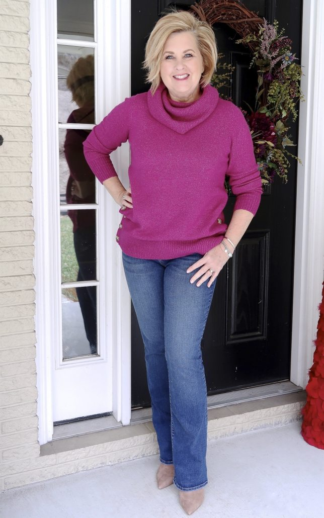 Fashion Blogger 50 Is Not Old wearing a bright fuchsia sweater with flare jeans and beige boots
