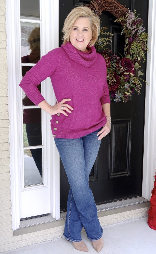 Fashion Blogger 50 Is Not Old wearing a bright colored fuchsia sweater and a pair of flare jeans
