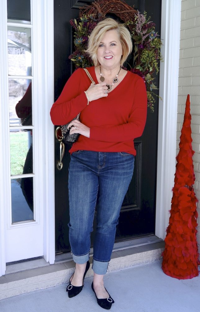 Jeans with a tweed cuff, flats with embellishments, and a red v neck sweater worn by Fashion Blogger 50 Is Not Old