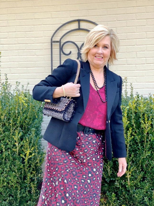 fashion blogger 50 is not old wearing a leopard print skirt and black knee boots