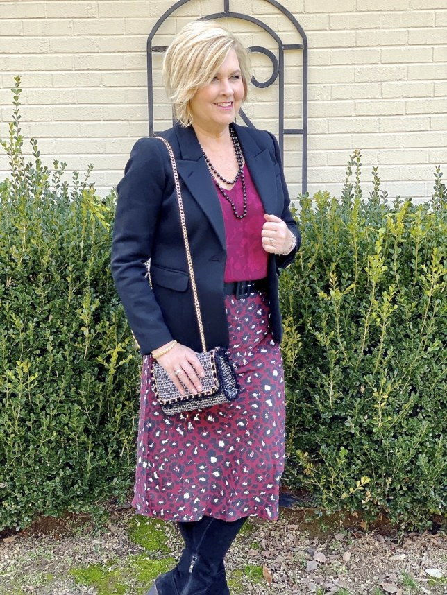Outfit for an office setting by fashion blogger 50 is not old. Leopard print skirt, a black blazer, a tweed handbag, and black knee boots